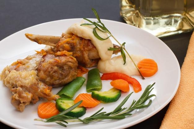 Ножки кролика, запеченные в белом вине с соусом бешамель на керамической тарелке с овощами и розмарином. диетическое мясо кролика, приготовленное в духовке.