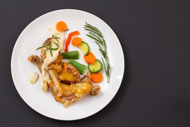 검은 배경에 야채와 로즈마리가 있는 세라믹 접시에 베샤멜 소스와 함께 화이트 와인에 구운 토끼 다리. 오븐에서 요리한 식이 토끼 고기. 복사 공간이 있는 상위 뷰입니다.