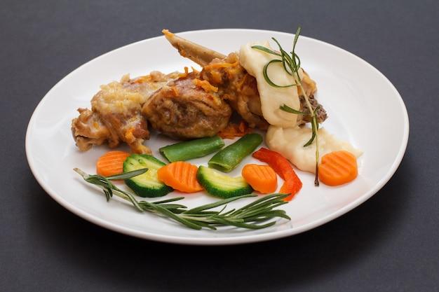 Кроличьи ножки, запеченные в белом вине с соусом бешамель на керамической тарелке с овощами и розмарином на черном столе. диетическое мясо кролика, приготовленное в духовке.