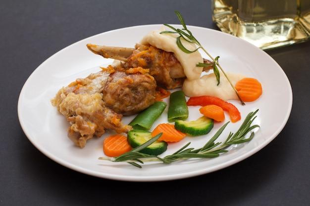 Ножки кролика, запеченные в белом вине с соусом бешамель, овощами и розмарином на керамической тарелке. диетическое мясо кролика, приготовленное в духовке.