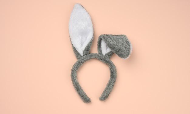 베이지 색 배경, 축제 배경, 평면도에 귀를 가진 머리에 토끼 마스크