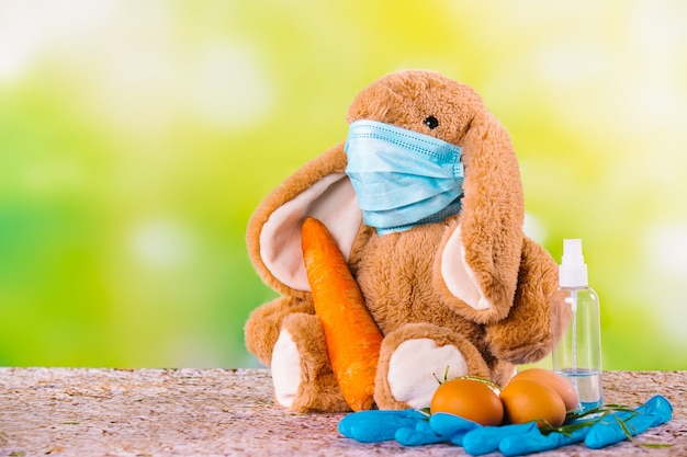 코로나 바이러스, 계란, 큰 당근, 보호 장갑 및 소독제에 대한 마스크가있는 녹색 장면의 토끼.