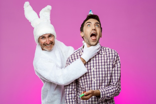 Rabbit smothering drunk man over purple wall. birthday party.