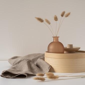Rabbit tail grass in beautiful tan vase, wooden storage box, neutral beige blanket against white wall.