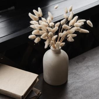 鍋にウサギノオの花束、テーブルの上に本を積み重ね