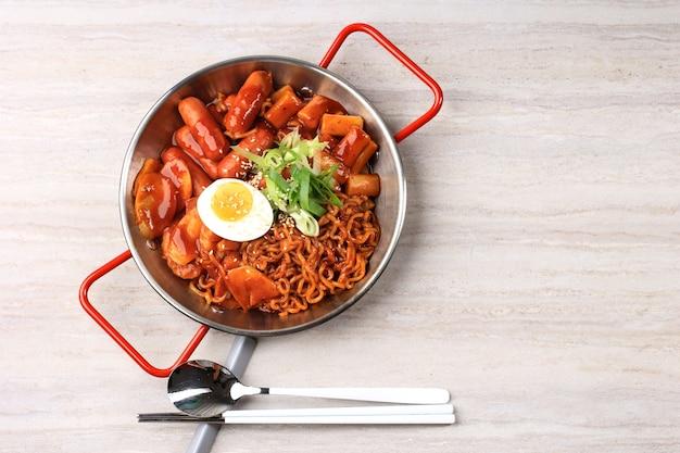 スパイシーな韓国ソースのラボッキ(ラーメンまたは韓国のインスタントラーメンとトッポッキ)、半熟卵とネギのスライス