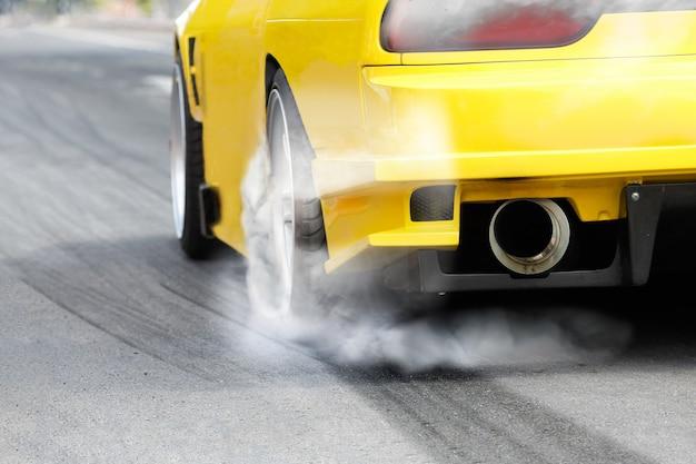 경주용 자동차는 경주를 준비하기 위해 타이어에서 고무를 태웁니다.