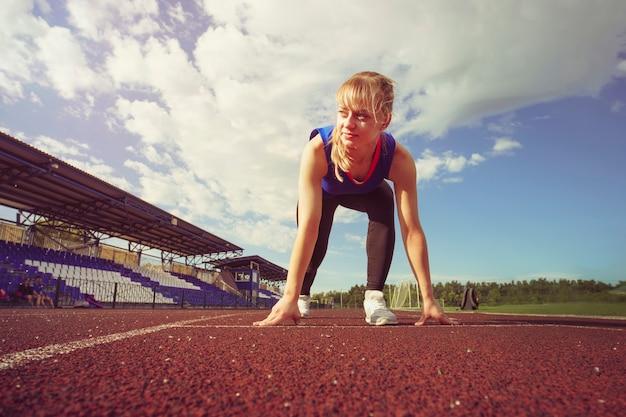 레이스 핏(race fit) 자신감 있는 여성이 달리기를 시작할 준비가 되었습니다. 멀리 보고 스프린트를 시작하려고 하는 여성 운동선수. 트랙에서 실행을 준비 하는 젊은 주자. 경기장에 경마장에 소녀 피트입니다.
