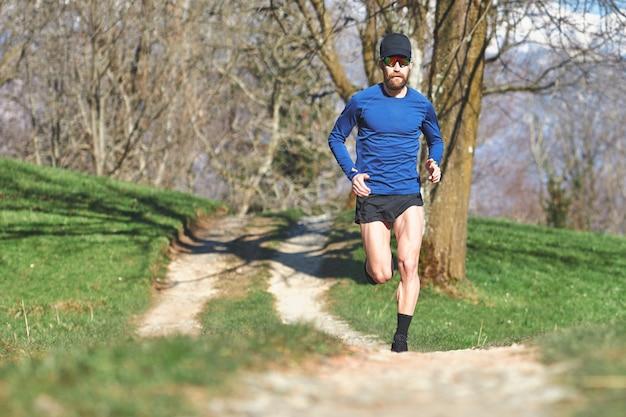 丘の未舗装の道路でレース。男は、ultarマラソンのために訓練します