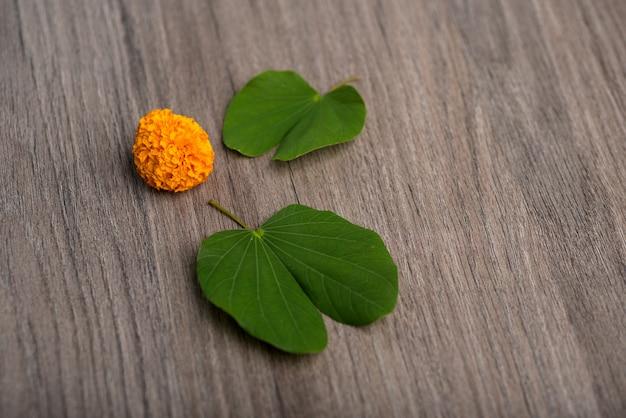 木製の背景にゴールデンリーフ(バウヒニアracemosa)とマリーゴールドの花を示すインドのお祭りdussehra。