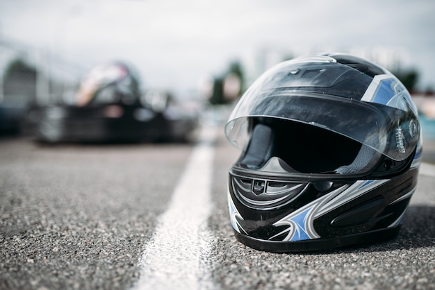 Racer helmet on asphalt, karting motor sport concept, go kart outdoor track, carting race