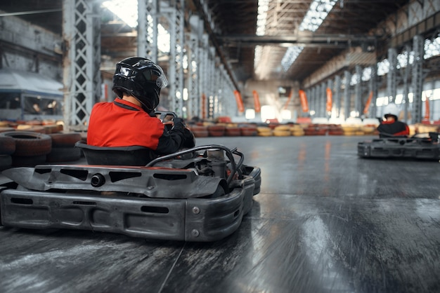 Racer in helmet driving go kart car, back view, karting auto sport indoor. speed race on close go-kart track with tire barrier. fast vehicle competition