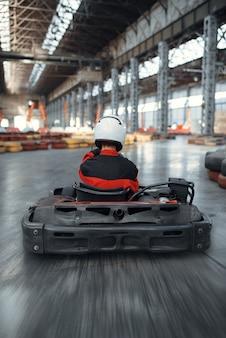 Racer in helmet driving go kart car, back view, karting auto sport indoor.