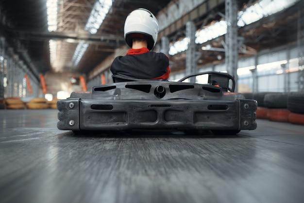 Racer in helmet driving go kart car