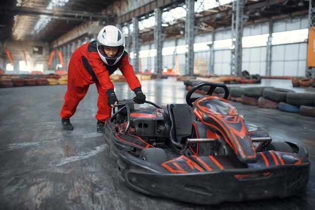 Racer in helmet pushing a go kart car, karting auto sport indoor.