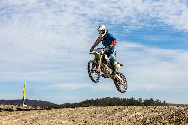 Racer on a motorcycle in flight, jumps and takes off on a springboard against the sky.