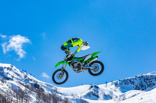 Racer on a motorcycle in flight in snowy mountains