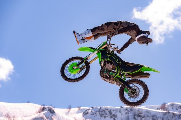 비행 중에 오토바이 경주, 점프와 눈 덮인 산에 대 한 발판에서 이륙