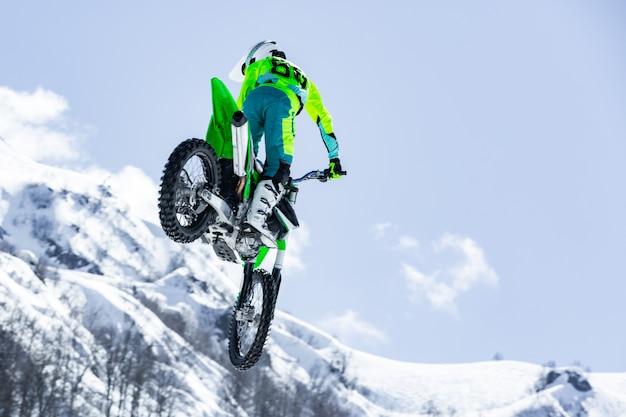 비행기에서 오토바이 경주, 점프와 눈 덮인 산에 대 한 발판에서 이륙