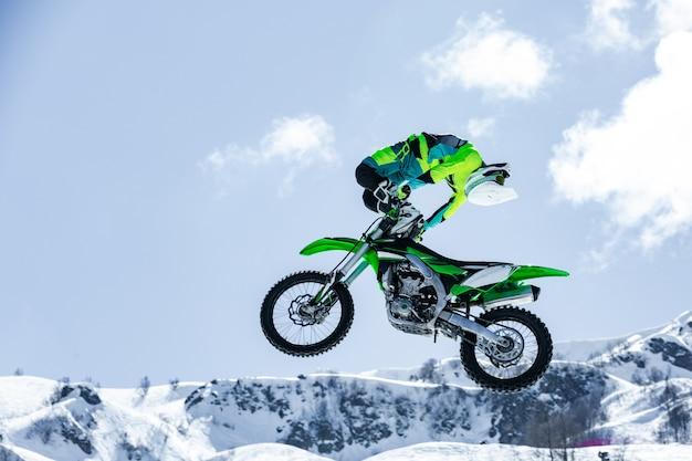 Гонщик на мотоцикле в полете, прыгает и взлетает на трамплине на фоне снежных гор