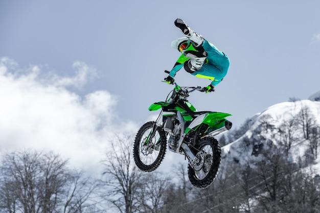 비행 중에 오토바이를 타는 레이서가 눈 덮인 산을 향해 발판에서 점프하고 이륙합니다.