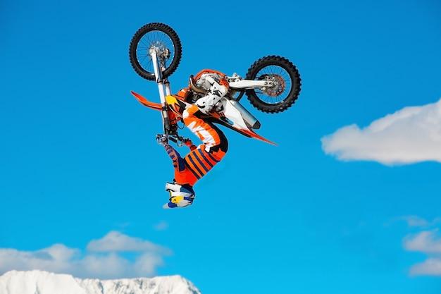 Гонщик на мотоцикле участвует в мотокроссе по пересеченной местности в полете, прыгает и взлетает на трамплин против неба.