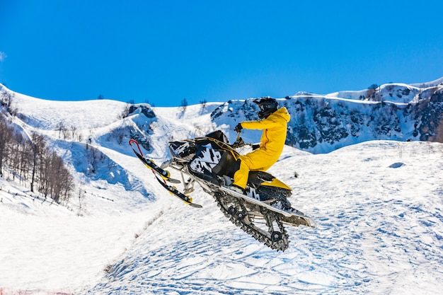 Racer on a snowcat in flight, jumps and takes off on a springboard against the snowy mountains