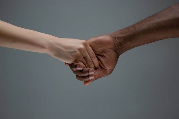 Racial tolerance. respect social unity. african and caucasian hands gesturing isolated on gray