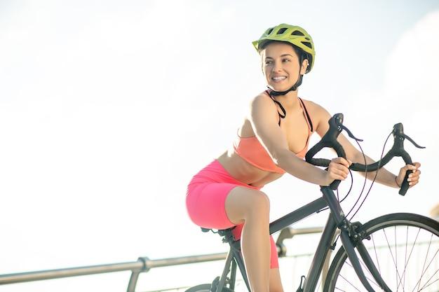 レーシングバイク。レーシングバイクに乗って明るいスポーツウェアの女性サイクリスト
