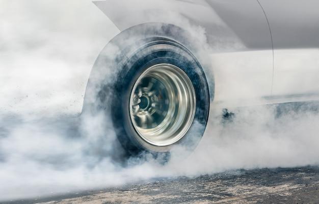 경주 용 자동차는 경주 준비를 위해 타이어에서 고무를 태 웁니다.