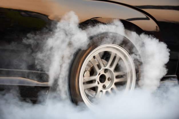 Racing car burns rubber off its tires in preparation for the race