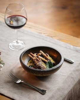 Стойка блюда из баранины в миске на сервированном столе с бокалом красного вина
