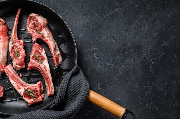 Каре ягненка, сырое мясо с костью. органическое мясо ягненка. черный фон. вид сверху. копировать пространство