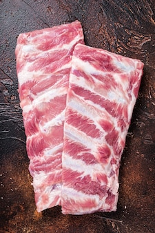 Rack of raw pork spare ribs on butcher table