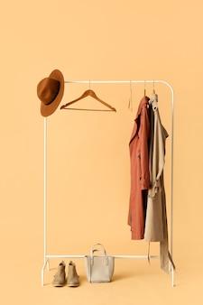 색상 배경에 옷, 모자, 신발 및 가방이 있는 랙