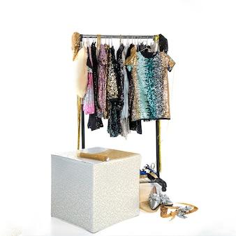 スマートで美しい女性のホリデードレス、ラインストーンの靴、スパンコールを備えたコートハンガー付きラック。イベント用の服、公演コンサート