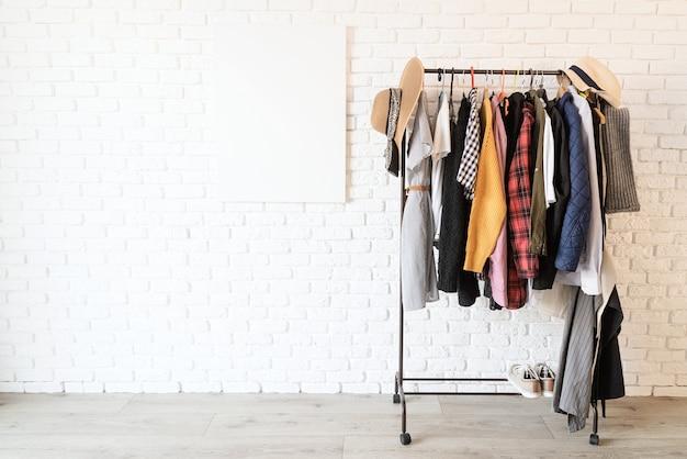 白いレンガの壁をモックアップするためのハンガーとフレームキャンバスにカラフルな服を着てラックに入れます。デザインのモックアップ