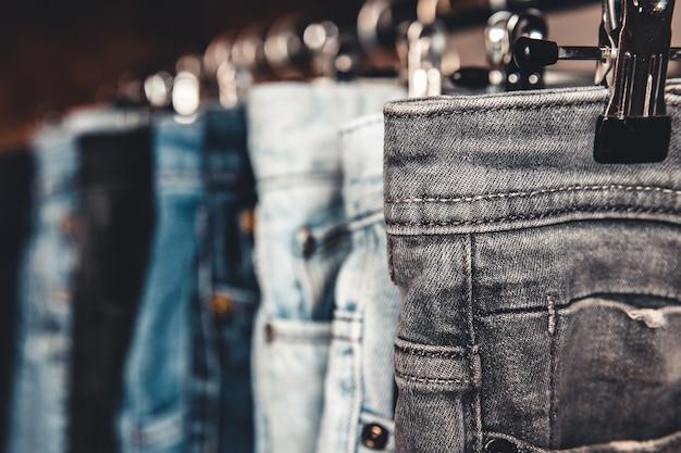 Стойка с разными джинсами на сером фоне