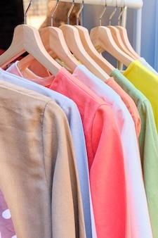 Вешалка с летней цветной одеждой на вешалках