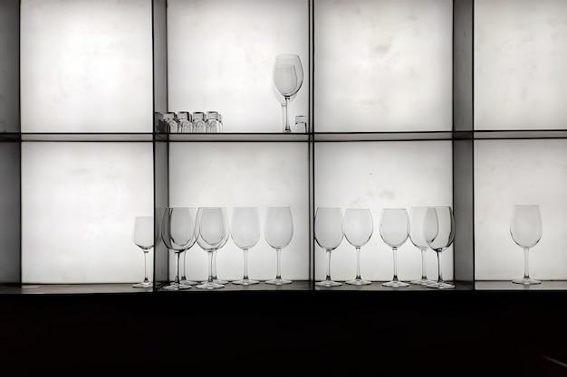 バーのさまざまなアルコール用の透明なグラスを備えたラック。白い背景に。