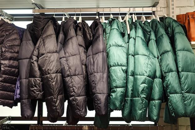 衣料品店でトレンディなグリーンとブラックの暖かいコートを着たラック。