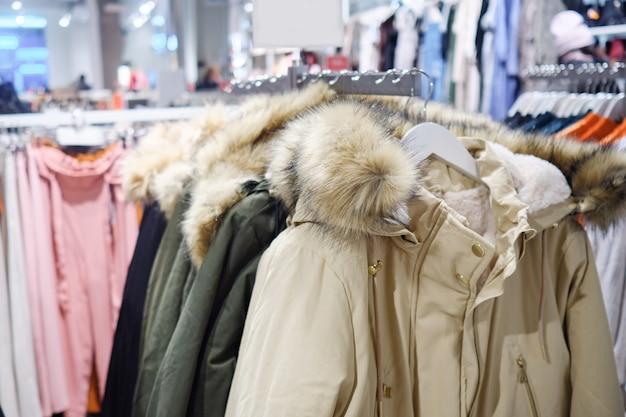 衣料品店のさまざまな色の流行の暖かいジャケットとラック