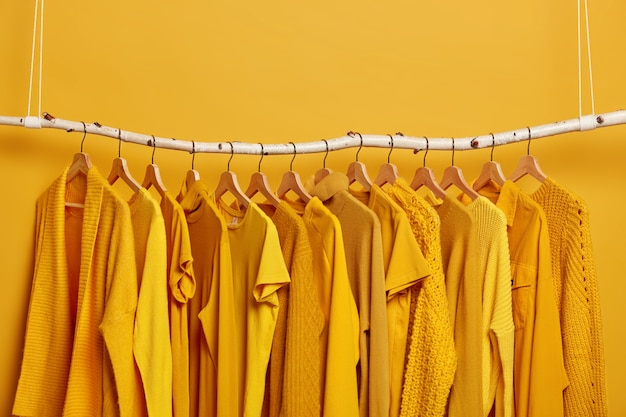 Rack with yellow clothes after dry cleaning. wardrobe with various outfits for different seasons. womens wear in fashion shop. selective focus. blank space above.