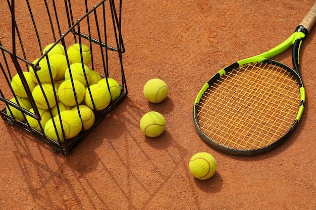 Ракетка и корзина с теннисными мячами на грунтовом корте