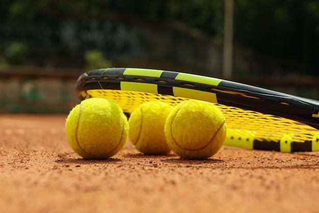 Ракетка и теннисные мячи на грунтовом корте