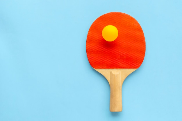 Ракетка для настольного тенниса с мячом на синем. пинг-понг спорт