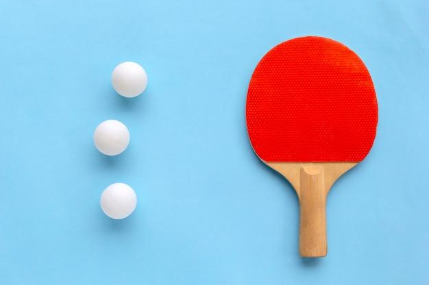 Ракетка для настольного тенниса с мячами на синем фоне.