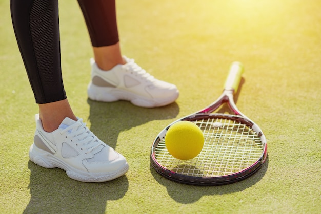 Racket for tennis, ball and female legs in sport sneakers on court close up