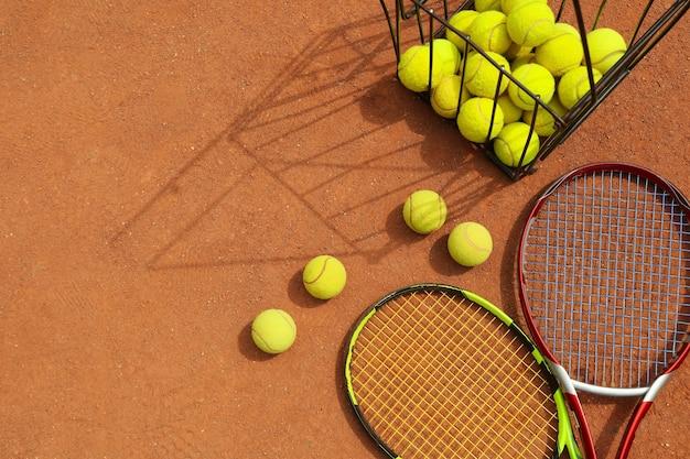 Ракетки и корзина с теннисными мячами на грунтовом корте
