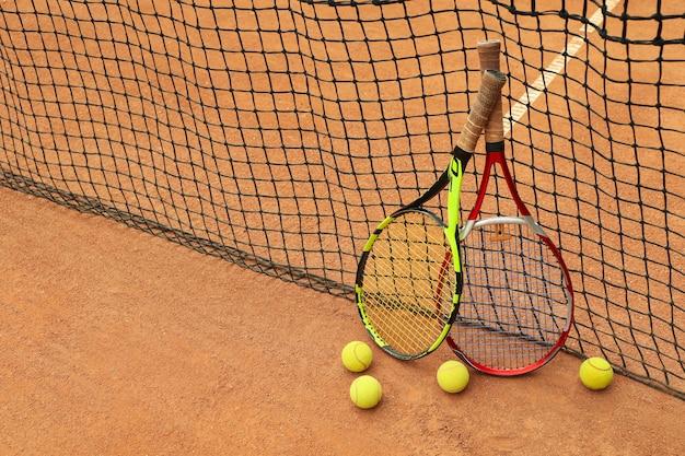 Ракетки и теннисные мячи против сетки на грунтовом корте